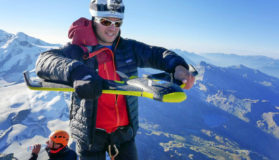 Man Standing With Geocurve Drone On Top Of Snowy Mountains